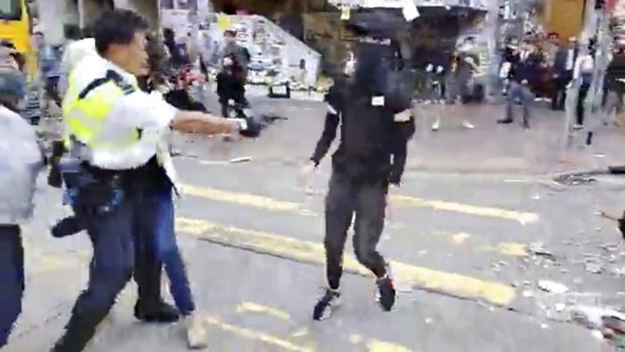 <i>ภาพที่ถ่ายจากคลิปวิดีโอ แสดงให้เห็นตำรวจผู้หนึ่ง (ซ้าย) ซึ่งกำลังจับกุมผู้ประท้วงรายหนึ่ง ยกปืนเตรียมยิงใส่ผู้ประท้วงอีกคนหนึ่ง (กลาง) ที่ตรงเข้ามาหา ที่ย่านไซหว่าน ของฮ่องกง วันจันทร์ (11พ.ย.) </i>