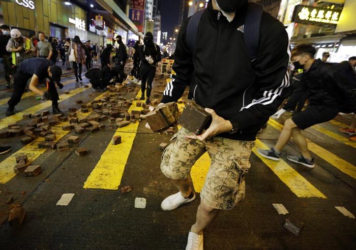 <i>ผู้ประท้วงรื้ออิฐปูทางเท้าออกมาใช้เป็นอาวุธ ขณะปะทะกันตำรวจที่ย่านมองก็อก </i>