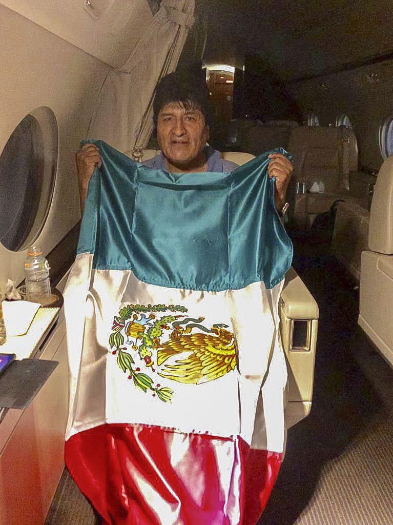 <i>เอโบ โมราเลส อดีตประธานาธิบดีโบลิเวีย ถือธงชาติของเม็กซิโก บนเครื่องบินซึ่งรัฐบาลเม็กซิโกส่งไปรับเขาเพื่อเดินทางไปลี้ภัย ภาพนี้รัฐมนตรีต่างประเทศ มาร์เซโล อีบราร์ด ของเม็กซิโก นำออกเผยแพร่ผ่านทางทวิตเตอร์ </i>