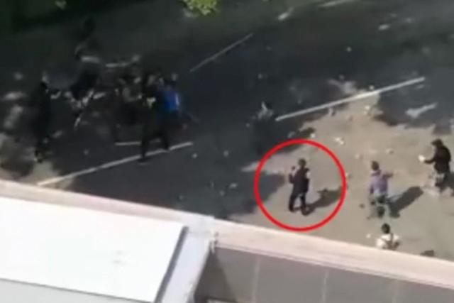 ชายวัย 70 ปี (วงกลม) กำลังยืนถ่ายภาพ ก่อนถูกขว้างด้วยก้อนอิฐ (ภาพจากคลิป )