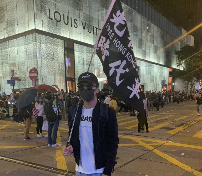 "<i>เบนจามิน ชาน ถือธงที่เขียนข้อความว่า ""ปลดแอกฮ่องกง การปฏิบัติแห่งยุคสมัยของเรา!"" (ภาพโดย เอเชียไทมส์) </i>"
