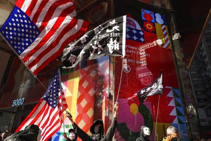 """<i>ผู้ประท้วงเรียกร้องประชาธิปไตยในฮ่องกง โบกธงชาติอเมริกัน และธงเขียนข้อความว่า """"ปลดแอกฮ่องกง การปฏิวัติแห่งยุคสมัยของเรา"""" ขณะเริ่มการประท้วงตอนบ่ายวันนี้ (8 ธ.ค.) </i>"""