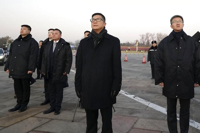 """<i>ภาพที่เผยแพร่โดยสำนักข่าวซินหวาของจีน แสดงให้เห็น คริส ถัง ผู้บัญชาการตำรวจฮ่องกงคนใหม่ (กลาง) ยืนพร้อมกับเจ้าหน้าที่คนอื่นๆ ขณะชมพิธีอัญเชิญธงชาติจีนที่จัตุรัสเทียนอันเหมิน ในกรุงปักกิ่ง เมื่อวันเสาร์ (7 ธ.ค.)  คริส ถัง กล่าวในวันเดียวกันว่า เขาจะใช้ทั้ง """"วิธีการแข็งกร้าวและวิธีการนุ่มนวล"""" ในการรับมือการประท้วงในฮ่องกง  เขาพูดกับผู้สื่อข่าวในกรุงปักกิ่งเช่นนี้ภายหลังการพบปะหารือครั้งแรกกับทางเจ้าหน้าที่จีน ตั้งแต่ที่เขาได้รับแต่งตั้งให้ดำรงตำแหน่งนี้เมื่อเดือนที่แล้ว </i>"""