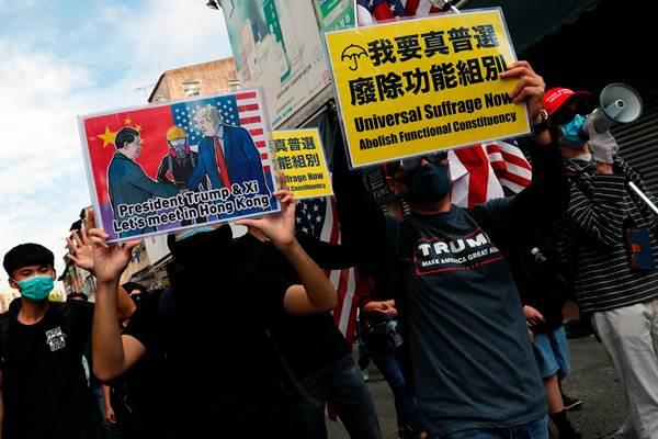 กลุ่มประท้วงต่อต้านรัฐบาลโบกธงชาติอเมริกาขณะเดินขบวนใน Sheung Shui เขตชายแดนฮ่องกงเมื่อวันอาทิตย์ที่ 5 ม.ค. 2020 (ภาพ รอยเตอร์ส)