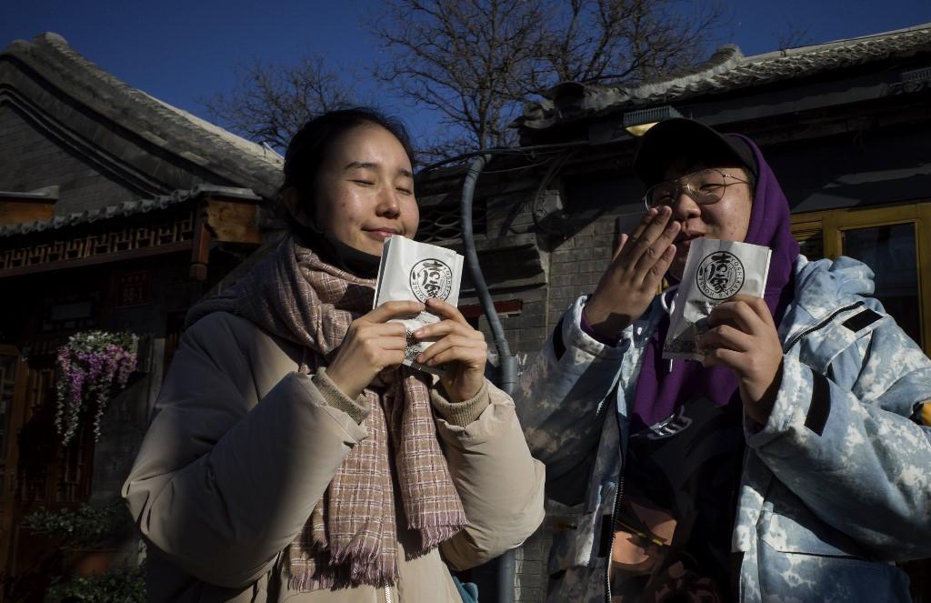 นักท่องเที่ยวจีนดมกลิ่นขนม (NOEL CELIS / AFP)