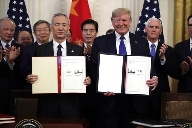 """ประธานาธิบดี โดนัลด์ ทรัมป์แห่งสหรัฐฯ (ขวา) และรองนายกรัฐมนตรีจีน หลิว เหอ ลงนามข้อตกลงการค้ากันเมื่อวันที่ 15 ม.ค. ที่ห้องอีสต์ รูม ทำเนียบขาว กรุงวอชิงตัน ทั้งสองฝ่ายตกลงแก้ไขปัญหาที่เป็น """"ความวิตกกังวลหลักๆ"""" ของกันและกัน (ภาพ เอพี)"""