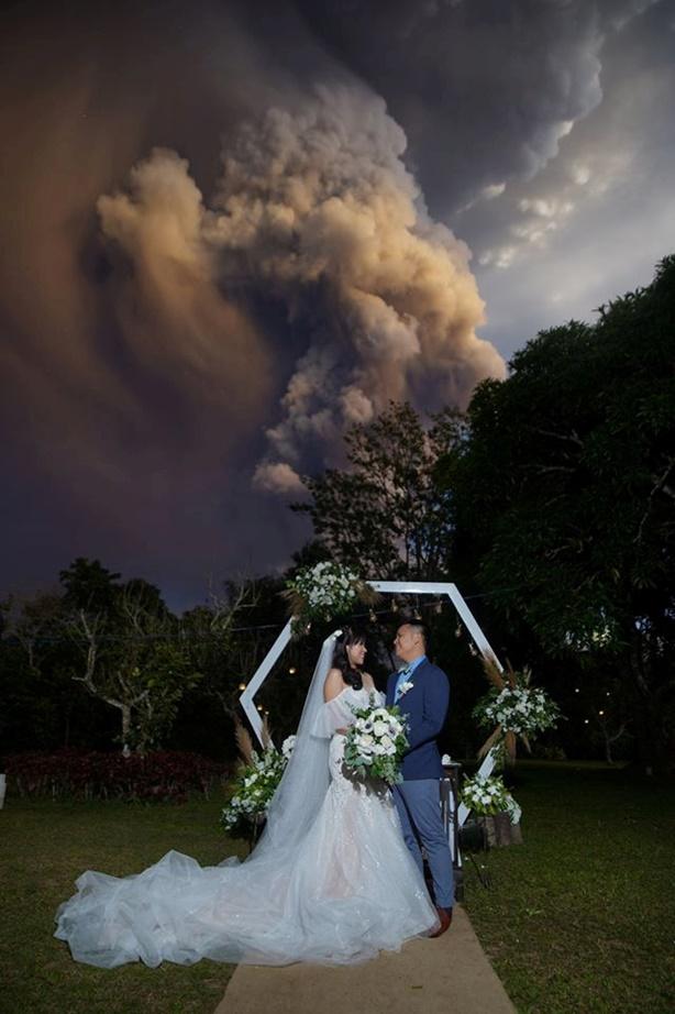 ภาพน่าสุดตะลึง คู่บ่าวสาวท้าความตายจัดงานพิธีสมรสในขณะที่ภูเขาไฟตาอัล(Taal )ของฟิลิปิปนส์กำลังพ่นเถ้าถ่านออกมาจากปล่องในฉากหลังที่อัลฟอนโซ (Alfonso) ในคาวิต (Cavite)  ภาพนี้ถูกถ่ายเมื่อวันที่ 12 ม.ค และเผยแพร่บนโลกโซเชียลมีเดีย ภาพประจำวันอังคาร(14 ม.ค) รอยเตอร์