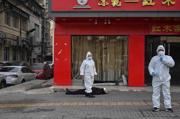 """In Pics: ด่วน! พบชาย """"นอนตาย"""" ข้างถนนในเมืองอู่ฮั่น  จนท.จีนชุดป้องกันชีวภาพรีบนำขึ้นรถ"""