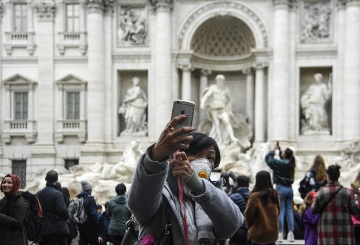 <i>นักท่องเที่ยวสวมหน้ากากอนามัย ขณะถ่ายภาพเซลฟี่ที่ลานน้ำพุเทรวี่ บริเวณใจกลางกรุงโรม เมืองหลวงของอิตาลี เมื่อตอนสิ้นเดือนมกราคมที่ผ่านมา </i>
