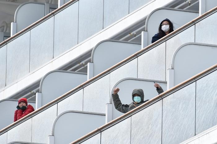 """<i>ผู้โดยสารบนเรือสำราญ """"ไดมอน์ ปรินเซส"""" ซึ่งถูกกักกันโรค โบกไม้โบกมือให้พวกผู้สื่อข่าว  ขณะเรือแล่นเข้าจอดเทียบท่าแห่งหนึ่งในเมืองโยโกฮามา ทางตอนใต้ของกรุงโตเกียวเมื่อวันพฤหัสบดี (6 ก.พ.)  เรือสำราญลำนี้วกกลับมายังโยโกฮามาตั้งแต่วันจันทร์ (3) ทว่าก่อนหน้านี้จอดทอดสมออยู่นอกท่าเรือ </i>"""