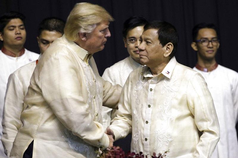 ประธานาธิบดี โดนัลด์ ทรัมป์ แห่งสหรัฐฯ จับมือทักทายประธานาธิบดี โรดริโก ดูเตอร์เต แห่งฟิลิปปินส์ ในงานเลี้ยงอาหารค่ำระหว่างการประชุมสุดยอดผู้นำอาเซียนเมื่อปี 2017 (แฟ้มภาพ)