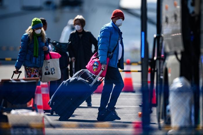 """ผู้โดยสารของเรือสำราญ """"ไดมอนด์ ปรินเซสส์"""" เตรียมตัวขึ้นรถบัส ภายหลังขึ้นมาจากเรือที่ถูกกักกันโรค  ณ ท่าเรือในเมืองโยโกฮามา เมื่อวันศุกร์ (21 ก.พ.)"""