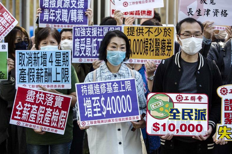 ชาวฮ่องกงออกมายืนชูป้ายประท้วงระหว่างที่ พอล ชาน รัฐมนตรีกระทรวงการคลัง กำลังแถลงร่างงบประมาณประจำปีต่อสภานิติบัญญัติฮ่องกงในวันนี้ (26 ก.พ.)