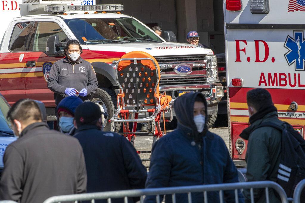 <i>นักเทคนิคการแพทย์ในทีมฉุกเฉิน ออกปฏิบัติหน้าที่โดยมีประชาชนเข้าแถวรออยู่ด้านนอกของโรงพยาบาลแห่งหนึ่งในย่านควีนส์ ของนครนิวยอร์ก เมื่อวันอังคาร (24 มี.ค.) เพื่อตรวจทดสอบว่าติดเชื้อไวรัสโคโรนาหรือไม่ ทั้งนี้นครนิวยอร์กเป็นจุดที่ไวรัสแพร่ระบาดหนักที่สุดในสหรัฐฯเวลานี้ </i>