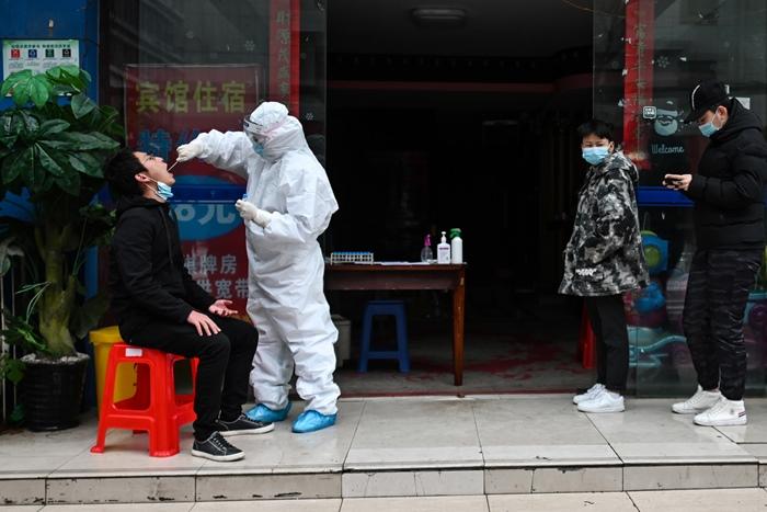 <i>ผู้ที่ต้องได้รับการตรวจทดสอบหาเชื้อโควิด-19 (ขวา) ยืนเข้าแถวรอ ขณะเจ้าหน้าที่สาธารณสุข ซึ่งอยู่ในชุดป้องกันโรคเต็มยศ  ใช้สำลีเก็บตัวอย่างจากลำคอของผู้ที่ต้องถูกตรวจ ณ คลินิกชั่วคราวที่บริเวณทางเข้าโรงแรมแห่งหนึ่งในเมืองอู่ฮั่น เมื่อวันอาทิตย์ (29 มี.ค.)  </i>