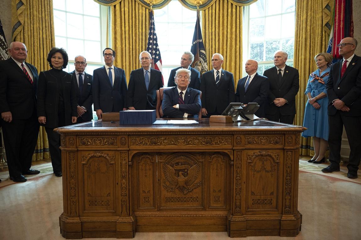 ประธานาธิบดีสหรัฐฯ โดนัลด์ ทรัมป์ กำลังลงนามบังคับใช้กฎหมายแคร์ส(the CARES act) ซึ่งเป็นกฎหมายงบฉุกเฉินเพื่อช่วยเหลือทางเศรษฐกิจแก่ชาวอเมริกันในวิกฤตโควิด-19 มูลค่า 2 ล้านล้านดอลลาร์ที่ห้องทำงานรูปไข่ประจำทำเนียบขาว ภาพประจำวันศุกร์(27 มี.ค) เอเอฟพี