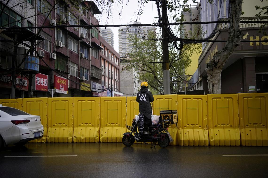 ภาพการใช้ชีวิตประจำวันของชาวอู่ฮั่น พนักงานส่งของรายหนึ่งรอที่ส่งอาหารผ่านเครื่องกีดขวางทางเข้าเขตพักอาศัยในตัวเมือง ภาพประจำวันอาทิตย์(29 มี.ค) รอยเตอร์