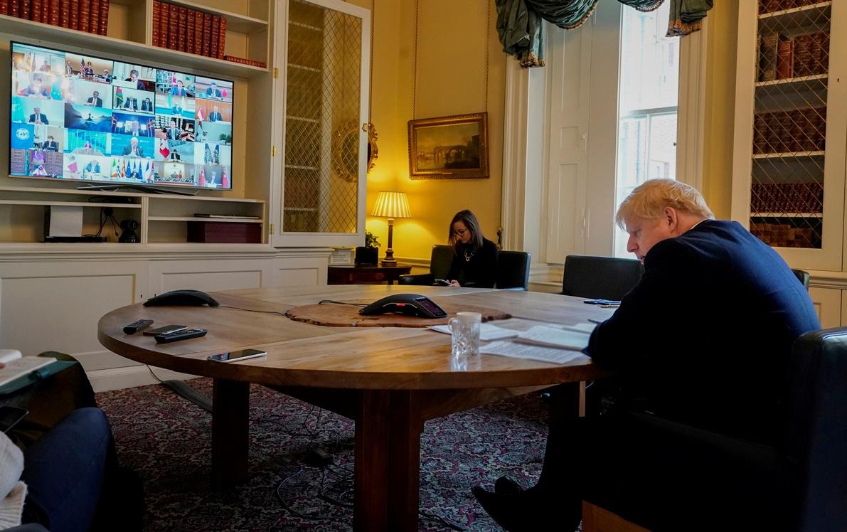 นายกรัฐมนตรีบอริส จอห์นสัน กำลังนั่งในห้องทำงานภายในบ้านเลขที่ 10 ถนนดาวนิงระหว่างการร่วมวิดีโอคอนเฟอเรนซ์กับผู้นำกลุ่ม G-20 คนอื่นๆ ทั้งนี้จอห์นสันออกมาแถลงผ่านทางทวิตเตอร์วันศุกร์(27 มี.ค)ว่า เขาป่วยติดเชื้อไวรัสโคโรนา ภาพประจำวันพฤหัสบดี(26 มี.ค) รอยเตอร์