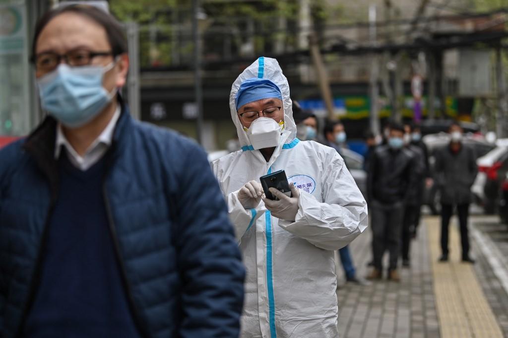 ประชาชนในอู่ฮั่นเข้าคิวรอรับการตรวจเชื้อโควิด-19 (Hector RETAMAL / AFP )
