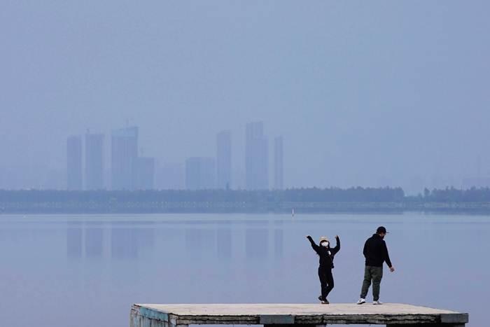 หญิงชาวอู่ฮั่นเต้นริมทะเลสาบตงหูเมื่อวันที่ 30 มี.ค. ฉลองออกจากบ้านได้เป็นวันแรกหลังจากที่ทางการผ่อนปรนมาตรการปิดเมือง (ภาพ รอยเตอร์ส)