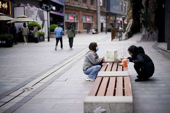 เด็กๆอออกมานั่งเล่นกินขนมของว่างริมถนนเมื่อวันที่ 31 มี.ค.หลังถูกล็อคตัวในบ้านสองเดือน (ภาพ รอยเตอร์ส)