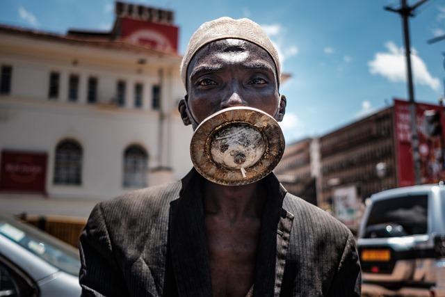 ชายใส่หน้ากากทางเลือกยืนถ่ายรูปในกรุงกัมปาลาของยูกันดา