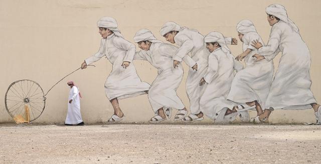 ชายชาวสหรัฐฯ อาหรับเอมิเรตคนหนึ่งกำลังเดินผ่านกำแพงลายกราฟฟิกในนครดูไบ เมื่อวันที่ 28 มีนาคม