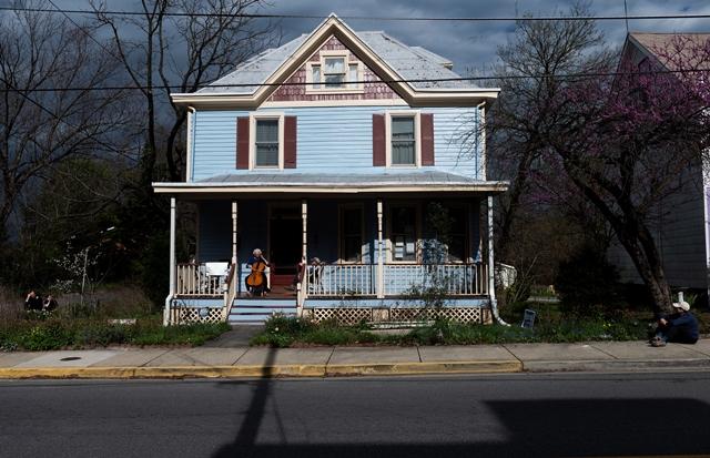 ผู้คนยืนมองนักเชลโล่ โจดี บีเดอร์ กำลังจัดคอนเสิร์ตประจำวันบริเวณระเบียงหน้าบ้านของเธอในเมืองเมาท์เรเนียร์ รัฐแมรีแลนด์ ใกล้กรุงวอชิงตัน ดี.ซี. เมื่อวันที่ 30 มีนาคม