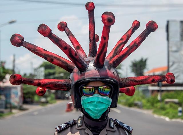 ตำรวจอินโดนีเซียสวมหมวกรูปไวรัสโควิด-19 เข้าร่วมการรณรงค์และฆ่าเชื้อรถจักรยานยนต์ของประชาชนในเมืองโมโจเกอร์โต จังหวัดชวาตะวันออก เมื่อวันที่ 3 เมษายน