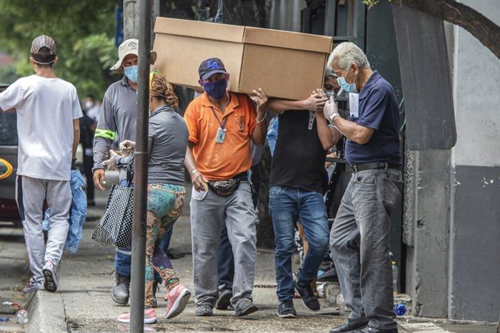 คนงานของสุสานแบกร่างผู้เสียชีวิตซึ่งบรรจุอยู่ในโลงทำด้วยกระดาษแข็ง เพื่อนำไปฝังที่สุสานกลาง ในเมืองกัวยากิล เมืองใหญ่ที่สุดของเอกวาดอร์ เมื่อวันจันทร์ (6 เม.ย.)  กัวยากิลกำลังกลายเป็นจุดฮอตจุดหนึ่งของโรคระบาดไวรัสโควิด-19 ในละตินอเมริกา  อย่างไรก็ตาม น่าจะมีผู้เสียชีวิตจำนวนหนึ่งซึ่งไม่ได้เกี่ยวข้องกับโรคนี้ ทว่าต้องตายเพราะไม่ได้รับการรักษา เนื่องจากโรงพยาบาลต่างๆ อยู่ในสภาพรับผู้ป่วยไม่ไหวแล้ว