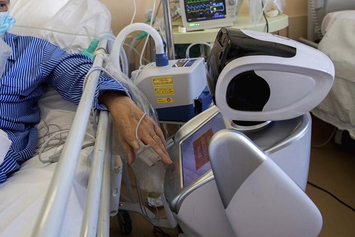 """<i>ผู้ป่วยโรคติดต่อเชื้อไวรัสโควิด-19 ซึ่งรับการรักษาในห้องไอซียู กดปุ่มโต้ตอบกับหุ่นยนต์ ณ โรงพยาบาล """"ออสเปดาเล ดิ ซีร์โคโล"""" ในเมือง วาเรเซ ประเทศอิตาลี เมื่อวันพุธ (8 เม.ย.)  โรงพยาบาลแห่งนี้มีหุ่นยนต์ 6 ตัว แต่ละตัวรับผิดชอบติดตามเฝ้าระวังและคอยช่วยเหลือคนไข้ 2 คน ทำให้แบ่งเบาภาระของเจ้าหน้าที่การแพทย์ลงไปได้มาก </i>"""