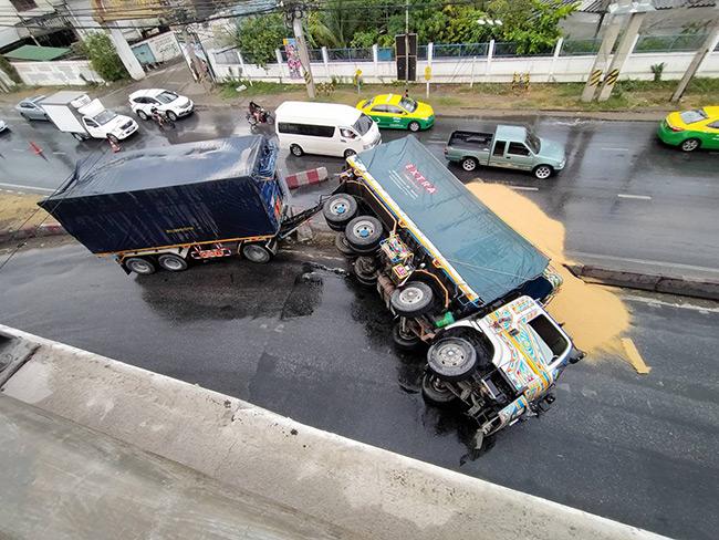 ฝนตกหนักถนนลื่นรถพ่วง 18 ล้อ พลิกคว่ำเทกระจาด ทำรถติดหนึบ