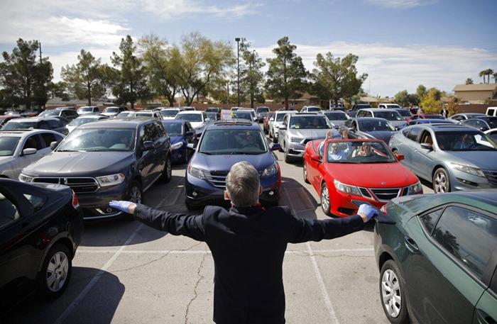 ศิษยาภิบาล พอล มาร์ค กูเลต สวดมนต์ให้ประชาชนที่อยู่ในรถยนต์ของพวกเขา ณ พิธีวันอีสเตอร์แบบไดรฟ์อิน ของโบสถ์อินเตอร์เนชันแนลเชิร์ชออฟลาสเวกัส ในเมืองลาสเวกัส รัฐเนวาดา เมื่อวันอาทิตย์ (12 เม.ย.)  เนื่องจากต้องทำตามกฎการเว้นระยะห่างทางสังคม เพื่อป้องกันการแพร่ระบาดของไวรัสโควิด-19  โบสถ์คริสต์นิกายต่างๆ ในสหรัฐฯจึงพลิกแพลงจัดพิธีอีสเตอร์กันไปหลายหลากรูปแบบ