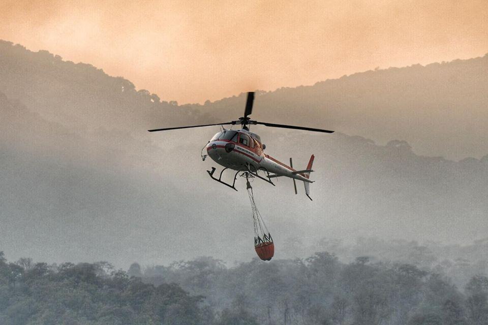 เจ้าหน้าที่นำเฮลิคอปเตอร์ขึ้นขนน้ำเพื่อดับไฟป่า ที่กำลังเผาลุกลามบริเวณพื้นที่เขาสูงชัน (ภาพ : เพจมูลนิธิสืบนาคะเสถียร)