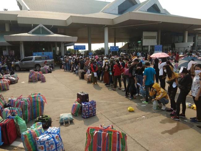 ภาพเมื่อเดือนมี.ค. 2563 เผยให้เห็นแรงงานชาวลาวจำนวนมากเข้าแถวหน้าด่านตรวจคนเข้าเมืองสะพานมิตรภาพไทย-ลาว เพื่อเดินทางข้ามฝั่งกลับประเทศ. -- AFP.