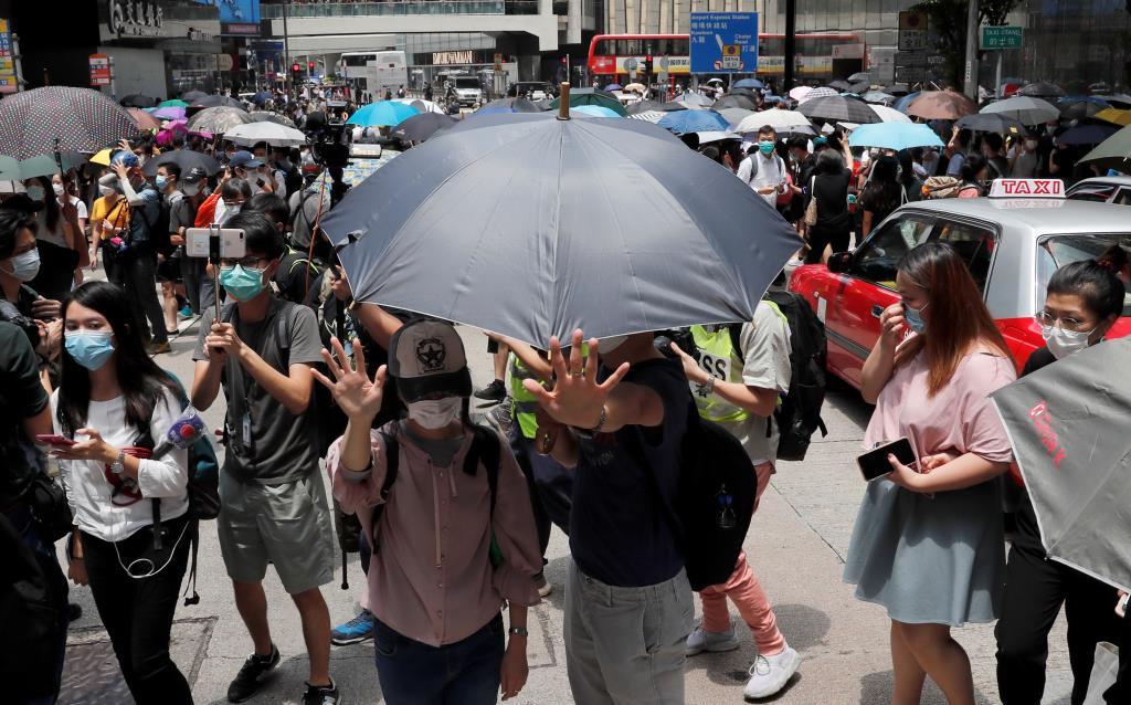 ผู้คนในฮ่องกงกลางร่มและสวมหน้ากากออกมาประท้วงในช่วงเที่ยงวัน ต่อต้านความเคลื่อนไหวของรัฐสภาจีนที่รับรองกฎหมายความมั่นคงแห่งชาติในฮ่องกง