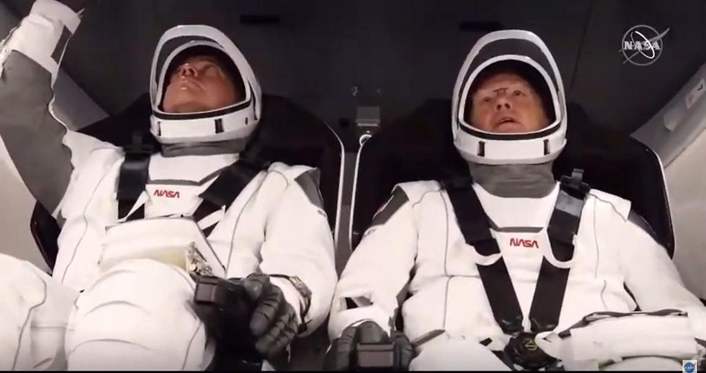 (ซ้าย) โรเบิร์ต เบห์นเกน (Robert Behnken) และ (ขวา) ดักลาส เฮอร์ลีย์ (Douglas Hurley) ในแคปซูลดรากอน (Crew Dragon spacecraft) ที่อยู่ด้านบนจรวดฟอลคอน 9 (Falcon 9) ณ ฐานปล่อยจรวด (NASA TV / AFP)