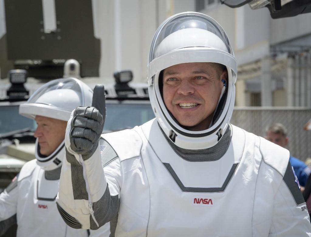 (หน้า) โรเบิร์ต เบห์นเกน (Robert Behnken) และ (หลัง) ดักลาส เฮอร์ลีย์ (Douglas Hurley) ในชุดอวกาศของสเปซเอกซ์ (SpaceX) ขณะออกจากศูนย์ปฏิบัติการนีล เอ.อาร์มสตรอง (Neil A. Armstrong Operations) และมุ่งหน้าสู่ฐานปล่อยจรวด 39เอ (Launch Complex 39A) ในศูนย์อวกาศเคนเนดี (Kennedy Space Center) ฟลอริดา สหรัฐฯ เมื่อ 30 พ.ค.2020 ตามเวลาท้องถิ่น เพื่อเตรียมพร้อมเข้าสู่แคปซูลดรากอน (Crew Dragon spacecraft) ในปฏิบัติการทดสอบนำส่งมนุษย์ในเที่ยวบินทดสอบสุดท้ายของสเปซเอกซ์และองค์การบริหารการบินอวกาศสหรัฐฯ (นาซา)  (Bill INGALLS / NASA / AFP)