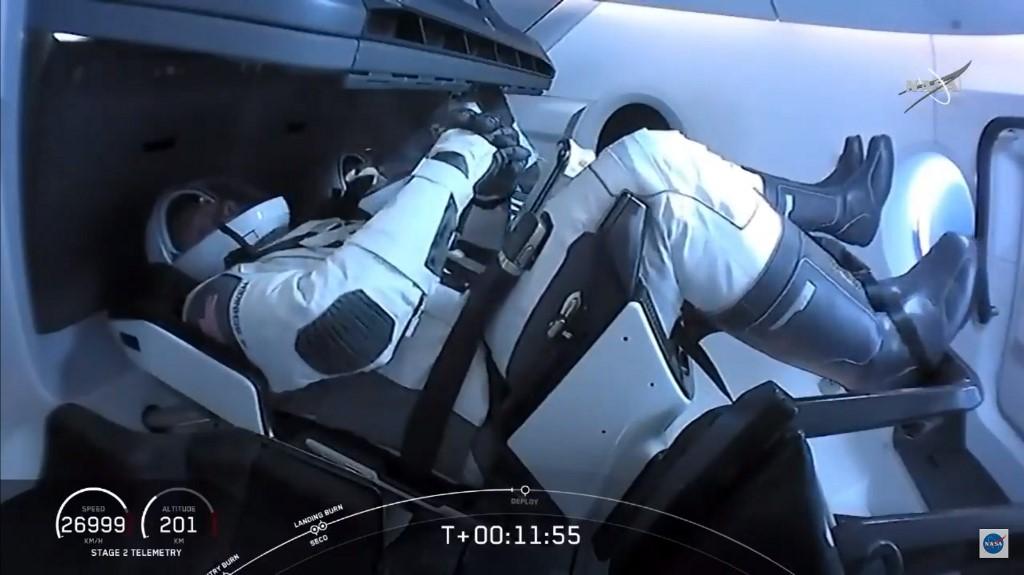 ภายในแคปซูลดรากอนหลังปล่อยตัวจากฐานปล่อยจรวดในศูนย์อวกาศเคนเนดี (หน้า) โรเบิร์ต เบห์นเกน (Robert Behnken) และ (หลัง) ดักลาส เฮอร์ลีย์ (Douglas Hurley) เข้าสู่วงโคจร (AFP / NASA TV )