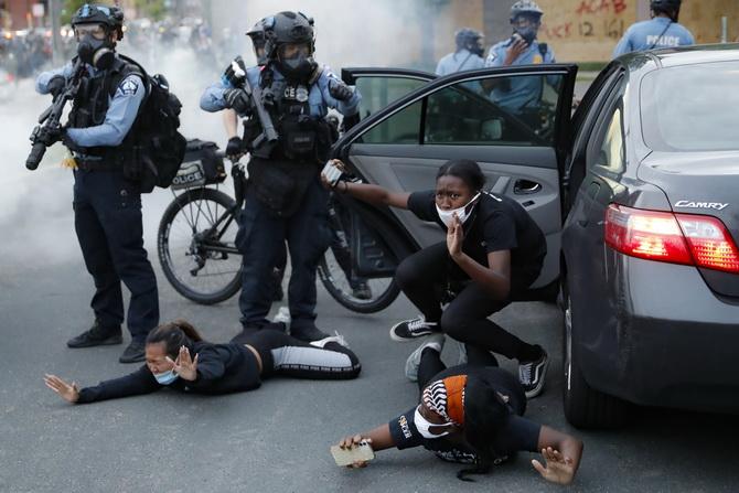 ผู้คนในรถยนต์ถูกตำรวจใช้อาวุธบังคับให้ออกจากรถและนอนราบกับพื้น  ระหว่างการประท้วงที่ถนนเซาท์วอชิงตัน ในเมืองมินนิอาโปลิส รัฐมินนิโซตา ของสหรัฐฯ เมื่อวันอาทิตย์ (31 พ.ค.)