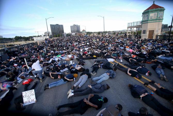 ผู้เดินขบวนประท้วงนอนลงกับพื้นบนสะพานเบิร์นไซด์บริดจ์ ในเมืองพอร์ตแลนด์ รัฐออริกอน เป็นเวลา 9 นาทีเมื่อคืนวันอังคาร (2 มิ.ย.) เท่ากับระยะเวลาที่ชายผิวดำ จอร์จ ฟลอยด์ ถูกตำรวจเมืองมินนิอาโปลิสใช้เข่ากดที่คอจนเขาเสียชีวิตไปในที่สุด