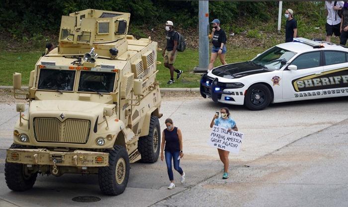 (ภาพถ่ายเมื่อ 1 มิ.ย.) ยานยนต์ทหารของหน่วยงานบังคับใช้กฎหมายจอดคุมเชิง ขณะที่ผู้ต้องการเข้าร่วมประท้วงเดินเข้าสู่จุดนัดชุมนุม ที่เมืองดัลลัส รัฐเทกซัส