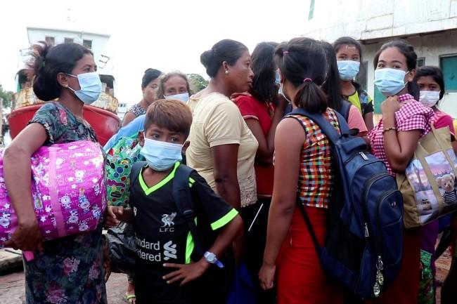 ชาวบ้านหอบหิ้วข้าวของอพยพจากเมืองระตีด่องมาถึงเมืองสิตตะเว เมืองเอกของรัฐยะไข่. -- Reuters.