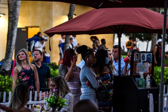 ผู้คนรอคิวอยู่บริเวณทางเข้าร้านอาหารแห่งหนึ่งที่ถนนโอเชียนไดรฟ์ เมืองไมอามี วันศุกร์ (26 มิ.ย.)
