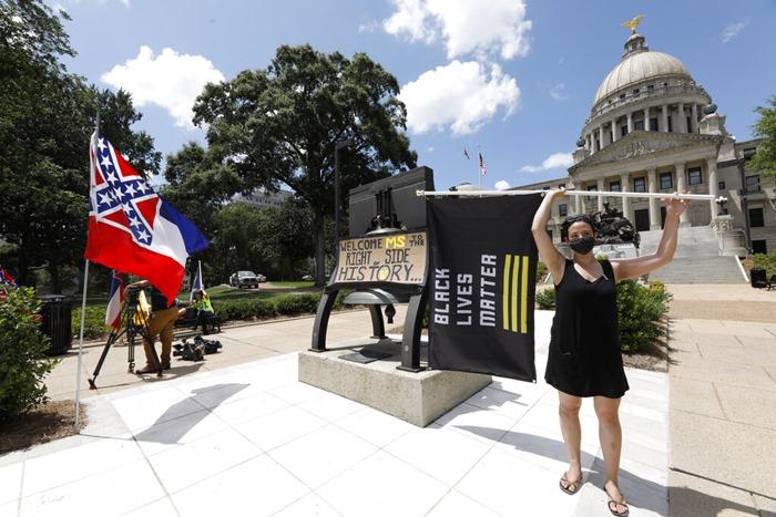 """ผู้ประท้วงโบกธง """"แบล็ก ไลฟ์ส แมตเทอร์"""" ใกล้ๆ กับธงของรัฐมิสซิสซิปปี  ทั้งนี้สภาทั้งสองของรัฐนี้ลงมติในวันอาทิตย์ (28 มิ.ย.) ให้เปลี่ยนแปลงธงประจำมลรัฐ โดยถอดสัญลักษณ์กากบาทดาว ของฝ่ายสมาพันธรัฐ ซึ่งอยู่ตรงมุมขวาบนของธงออกไป"""