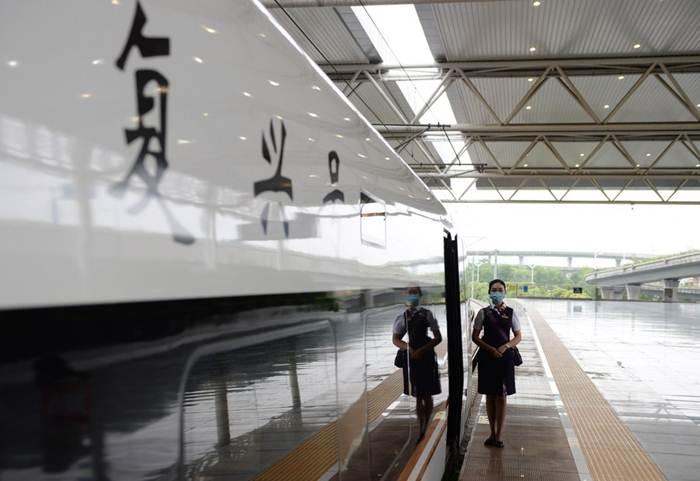 พนักงานต้อนรับบนรถไฟรอผู้โดยสาร ณ ประตูขบวนรถไฟความเร็วสูง หมายเลข G9394 ที่เตรียมเดินทางจากสถานีรถไฟเหอเฝยตอนใต้ของมณฑลอันฮุยสู่นครหางโจวของมณฑลเจ้อเจียงบนทางรถไฟความเร็วสูงสายซางชิว-เหอเฝย-หางโจว วันที่ 28 มิ.ย. 2020 (ภาพซินหัว)