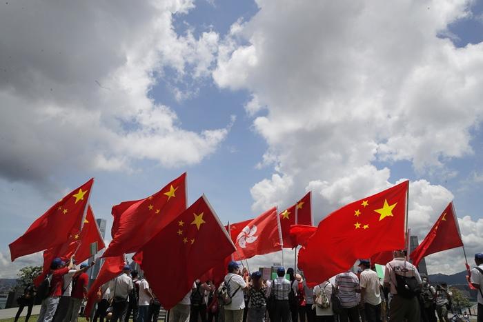 กลุ่มผู้สนับสนุนจีน ออกมาโบกธงชาติจีนและธงฮ่องกง ระหว่างการชุมนุมที่ฮ่องกงเมื่อวันอังคาร (30 มิ.ย.) เพื่อเฉลิมฉลองการออกกฎหมายความมั่นคงแห่งชาติสำหรับฮ่องกง