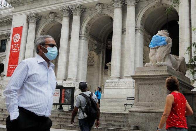 รูปปั้นสิงโตบริเวณหน้าหอสมุดสาธารณะสาขานิวยอร์ก ถูกคลุมปากด้วยหน้ากากป้องกันการแพร่ระบาดของไวรัสโควิด-19