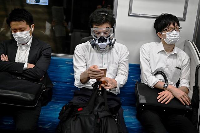 ชาวญี่ปุ่นคนหนึ่งสวมหน้ากากและแว่นตาป้องกันเต็มพิกัด ระหว่างโดยสารรถไฟในกรุงโตเกียว