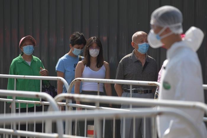 (ภาพจากแฟ้ม) ผู้คนเข้าแถวรอรับการตรวจทดสอบโรคโควิด-19 ณ สถานีตรวจแห่งหนึ่งในกรุงปักกิ่งเมื่อวันที่ 30 มิถุนายน
